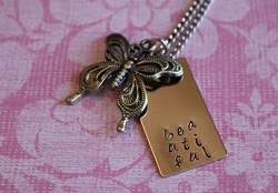 Buttefly Necklace with Beautiful stamped onto a tag behind the butterfly