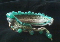 Back side of Novica handmade beaded bracelet in blue beads, crochet in white outlined in blue crochet